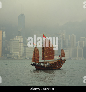 Traditional style Chinese sailing junk passes along the misty waterfront in 1989 in Victoria Harbour Hong Kong Island - Stock Photo