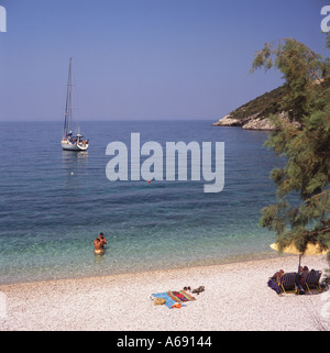 Couple in the sea at Makris Gialos Beach & bay with sailing yacht moored off shore Zakynthos Island The Greek Islands - Stock Photo
