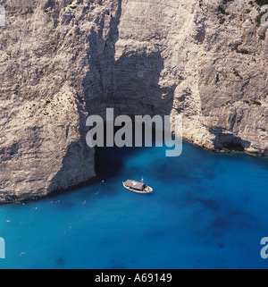 View down over spectacular cove and cliffs of Shipwreck Bay with people swimming off boat Zakynthos The Greek Islands - Stock Photo