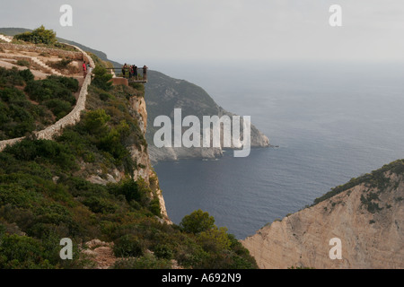 Tourists standing on [cliff top] viewing platform high above famous [Shipwreck Bay], [Smugglers Cove], Zante, Zakynthos, - Stock Photo