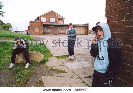Teenage children hanging around outside youth club run down council housing estate Bradford UK - Stock Photo