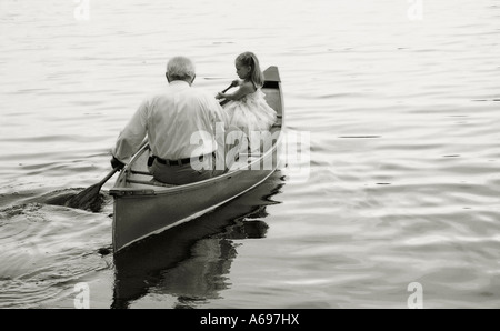Grandfather and granddaughter paddling in canoe on lake. - Stock Photo