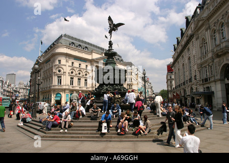 UK London Piccadilly Circus tourists sat beneath statue of Eros - Stock Photo