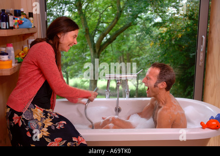 A COUPLE IN THE BATHROOM OF A MODERN HOUSE WITH SLIDING WINDOWS UK - Stock Photo