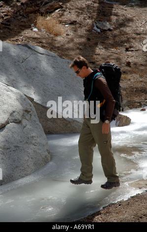 Man walking on thin ice of frozen stream - Stock Photo
