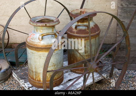 Milk pails on a spoked wheel wagon displayed outside Timeless Wonders Antique store. 'Otter Tail' Minnesota USA - Stock Photo