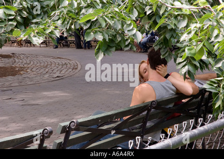 Two lovers kissing in the park. Space for copy. - Stock Photo