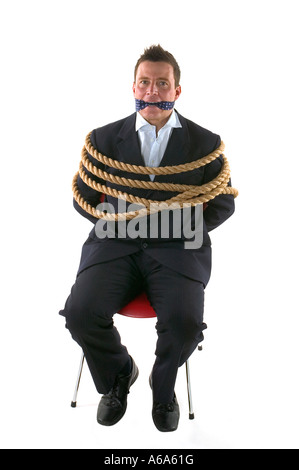 Businessman tied up with rope and gagged with his own tie isolated on a white background - Stock Photo