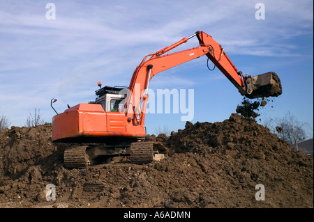 Construction digger on a mound of earth bucket tipping - Stock Photo