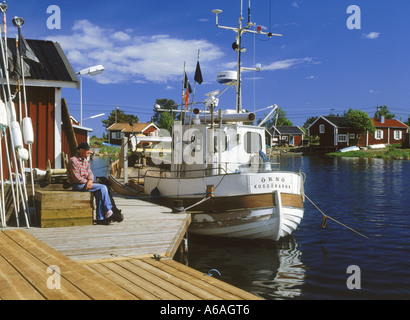 Fisherman and his fishing boat at Baltic Sea island village of Kuggoren on Sweden East Coast