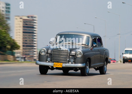 Classic American Automobile drives along Malecon Sea front Havana. - Stock Photo