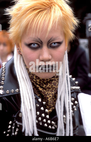 A girl with beady eyes and orange hair stares at the camera during 'cosplay,' or costume play in Harajuku Tokyo - Stock Photo