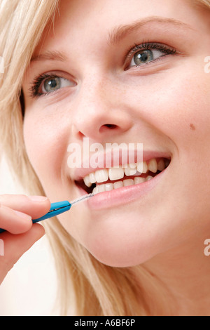 woman cleaning teeth with interdental brush - Stock Photo