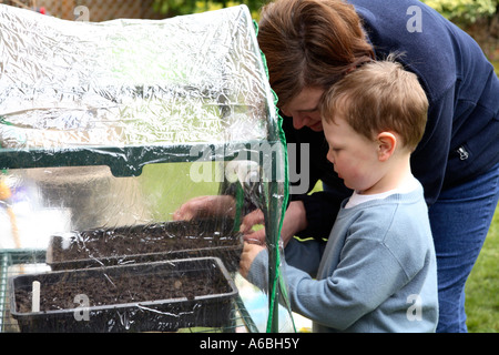 Mother helping her young son place planted seed trays into small plastic greenhouse for germination in early spring