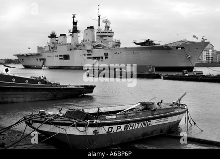 HMS ILLUSTRIOUS, moored at Wood Wharf, Greenwich, with local fishing boats     in the foreground. Image converted - Stock Photo