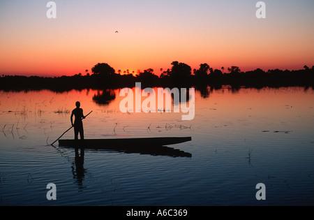 Botswana people Bayei mokoro poler at sunset in the Okovango Delta Okovango Botswana - Stock Photo