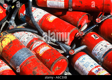Old used extinguishers in a pile - Stock Photo