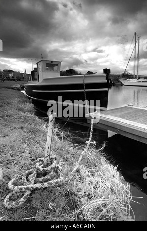 Mono image of a small fishing boat safely moored at Turf Lock on Exeter Ship Canal on a stormy overcast day with - Stock Photo
