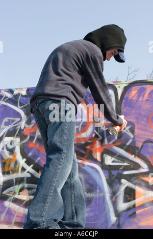 Young male youth using spray can to graffiti on wall - Stock Photo