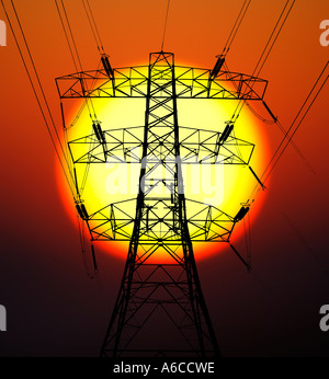 A High Voltage Pylon against a Glowing Sun - Stock Photo