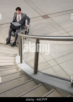 Man in Wheelchair Looking at Staircase - Stock Photo