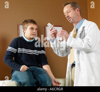 Doctor Giving Boy Needle - Stock Photo