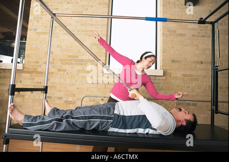 Man Exercising With Pilates Instructor - Stock Photo