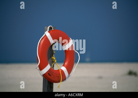 Life preserver hanging on a wooden post - Stock Photo