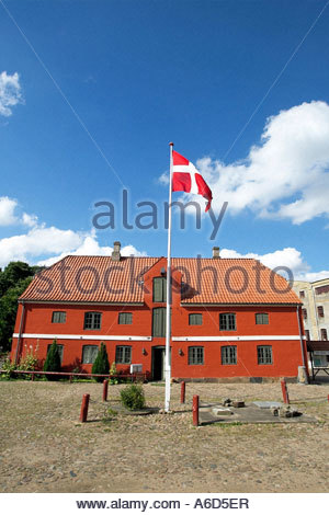 Red Building with the Danish flag in front of it - Stock Photo
