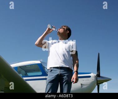 A man drinking from a bottle of water beside a single engine aircraft. - Stock Photo