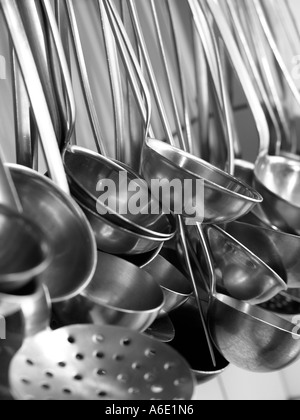 Black and white monochrome image of collection of ladles dippers spoons utensils hanging in professional kitchen - Stock Photo