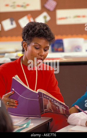 African American female teacher reading to students - Stock Photo