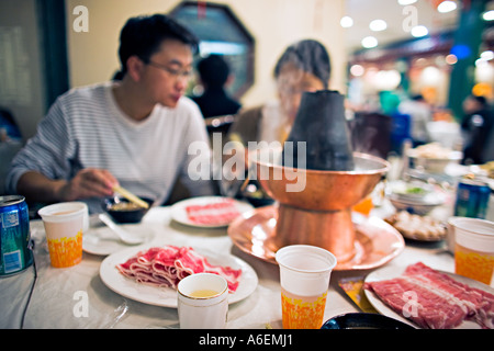 CHINA BEIJING Young Chinese couple enjoying Mongolian hotpot meal with a variety of food and condiments at popular - Stock Photo