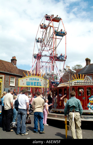 Ferris wheel rotates high above the crowd at a small village fete in Dorset - Stock Photo