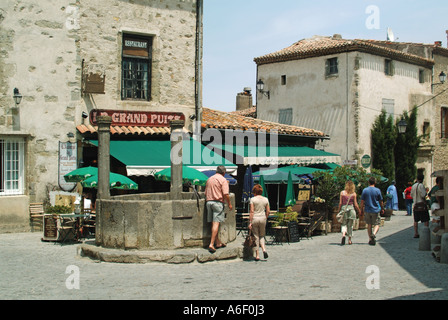 Carcassonne well with tourists in street scene in fortified medieval town pavement bar with sun brolly tables and - Stock Photo
