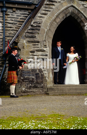 SCOTLAND Balquhidder Male bagpiper play outside 19th century parish church bride and groom stand in arch wedding - Stock Photo