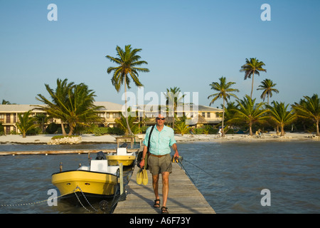 BELIZE Ambergris Caye Adult male fly fisherman walk down dock toward boat hold rod and wading boots - Stock Photo