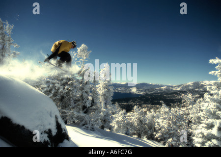 A snowboarder jumping in powder snow above Lake Tahoe in Nevada - Stock Photo