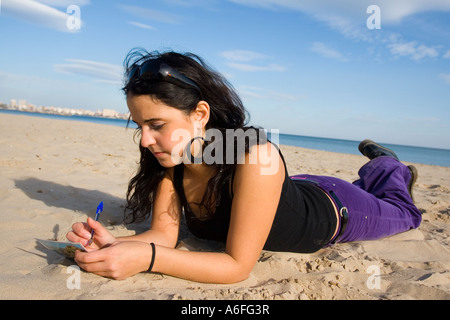Young woman lying on beach. - Stock Photo