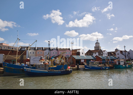 Town Camber fish docks with colourful fishing boats in water and modern housing development Old Portsmouth Hampshire - Stock Photo