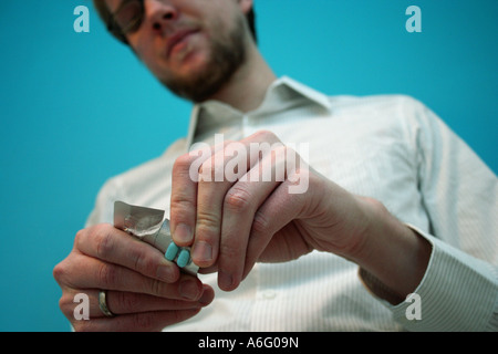 Young bearded man with glasses stands about to open a package of blue pills - Stock Photo