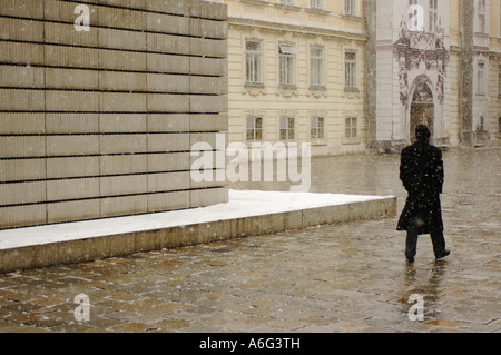 Austria Vienna Man walking next to Jewish Memorial in snowstorm - Stock Photo