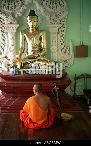 monk during meditation in front of a buddha statue, Burma, Yangon - Stock Photo