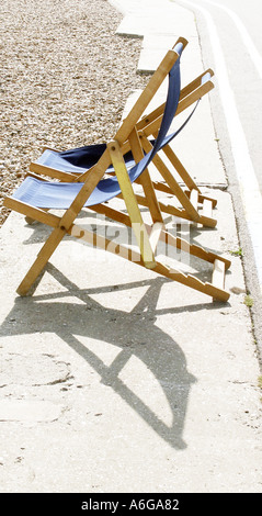 deck chairs wood pine frames twin 2 two row seaside sea beach shingle look out toward blue edge front day sunny - Stock Photo