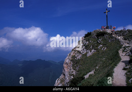 Summit cross and mountain hikers at Hochfelln mountain agains blue sky; Chiemgau, Bavaria, Germany - Stock Photo
