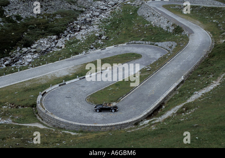 Black Volkswagen Beetle Cabriolet on winding serpentines of the old St. Gotthard pass (Switzerland) - Stock Photo