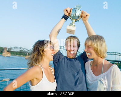 Women and man with trophy - Stock Photo