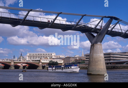 Millennium Bridge (architect: Norman Foster & Partners; 2000) over River Thames, with tour boat, London, England - Stock Photo