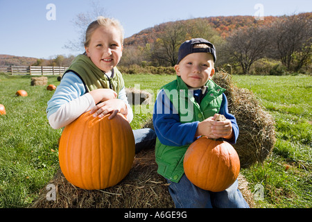 Boy and girl in field with pumpkins - Stock Photo