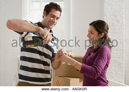 Couple having champagne in new apartment - Stock Photo